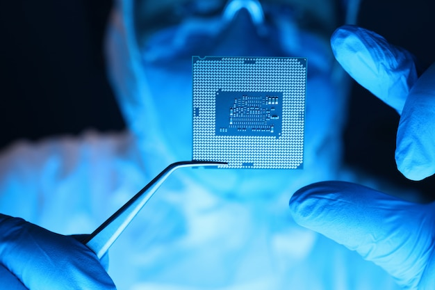 Man in uniform holds microprocessor with forceps