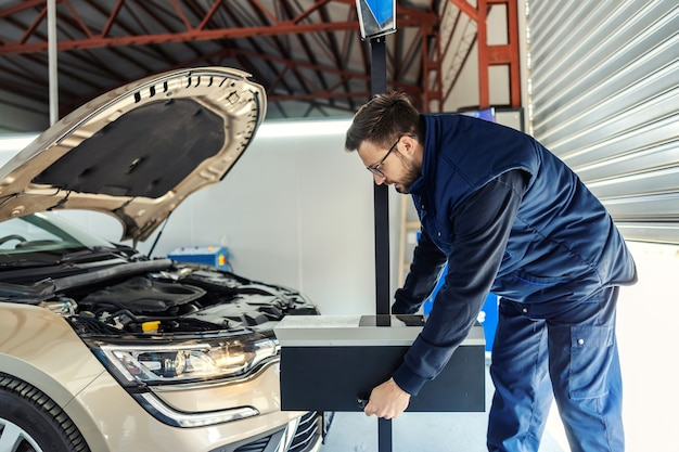 A man in uniform holds a toolbox in his hands in a workshop in front of a car with an open hood