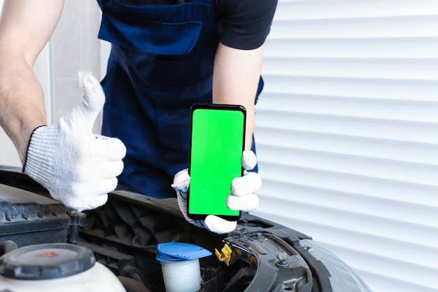 A man in uniform repairs a car and holds a smartphone with a green screen and shows like