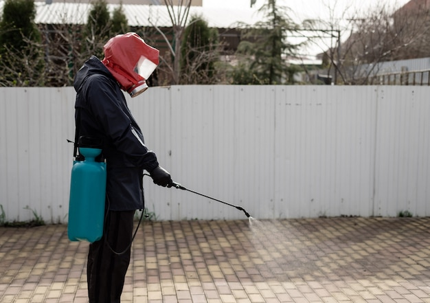 A man in a uniform and a respirator, treats the street with a disinfectant using a spray gun preventive measures coronavirus covid-19