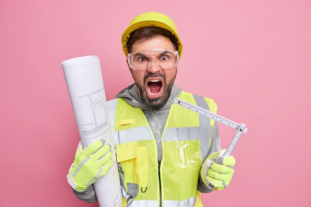 L'uomo in uniforme con casco di sicurezza occhiali trasparenti tiene il metro a nastro e il progetto arrotolato urla con fastidio isolato sul muro rosa