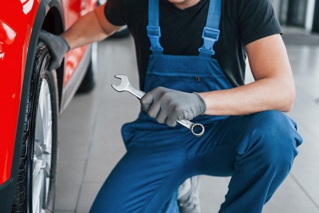 Man in uniform sits with wrench in hand near broken automobile. conception of car service