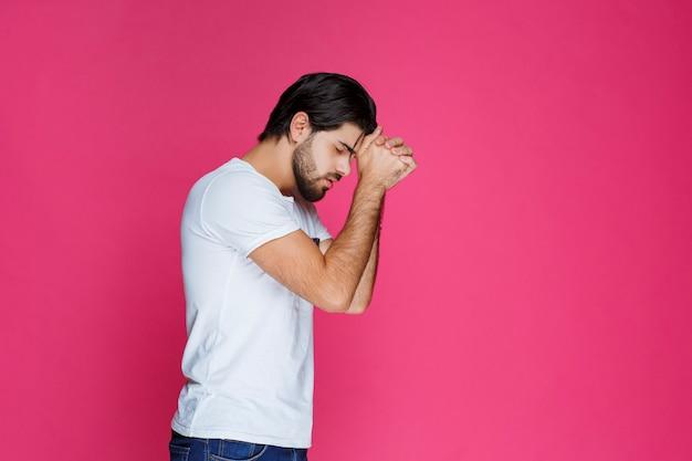 Человек сжимает кулаки и о чем-то молится.
