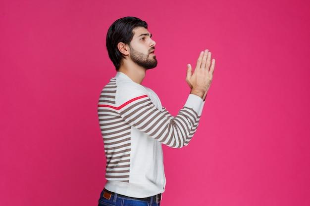 手を合わせて祈る男。