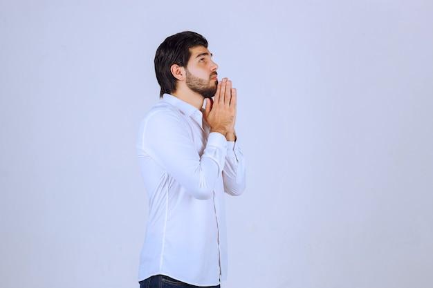 Uomo che unisce le sue mani e prega.