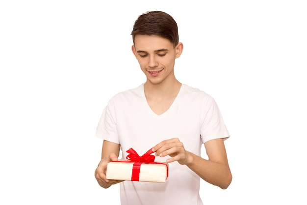 Man unleashes a ribbon bow. surprise concept. isolated front view on white background, happy guy