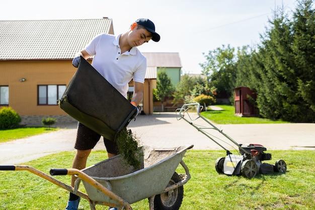 Man unloads mowed grass from a lawns mower catcher into wheelbarrow