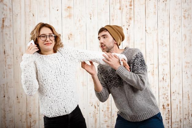 Человек нервирует свою подругу, говоря по телефону через деревянную стену