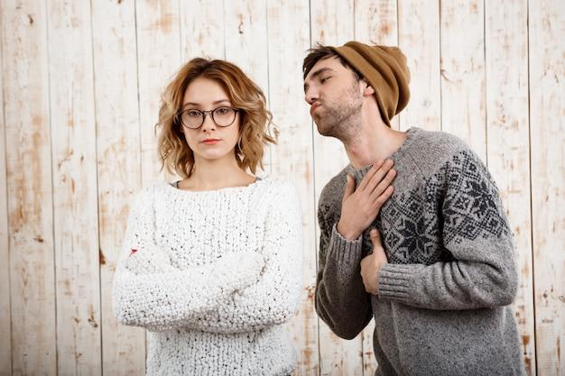 Мужчина нервирует свою подругу скрещенными руками на деревянной стене