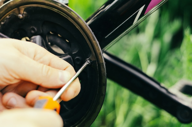 A man unscrews bolts with an orange screwdriver on a mountain bike chain
