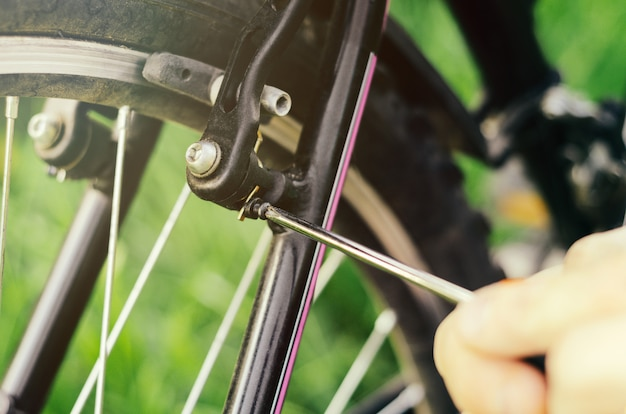 A man unscrews the bolts with a screwdriver on the mount wheel brakes of a mountain bike on the of grass
