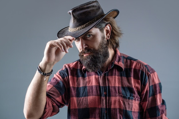 면도하지 않은 카우보이 남자. 아메리칸 카우보이. 가죽 카우보이 모자. 세로 젊은 남자