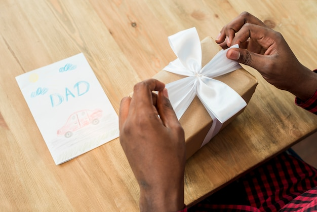 Man untying bow on gift box near greeting card