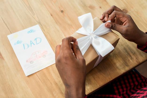 Uomo sciogliere arco sul contenitore di regalo vicino a biglietto di auguri