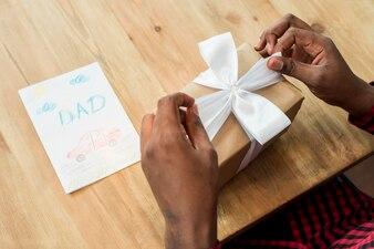 Человек развязывает лук на подарочной коробке возле открытки