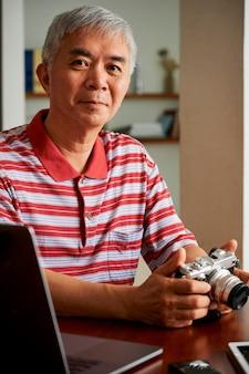 ノートパソコンのカメラから写真をアップロードする男
