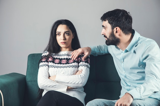 The man upset offended woman sitting in sofa