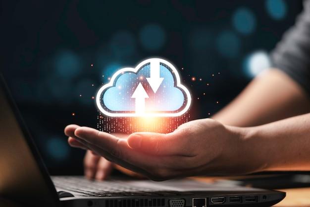 Человек использует компьютерный ноутбук и руку, держащую виртуальные облачные вычисления для загрузки загружаемых данных, концепции преобразования технологий.