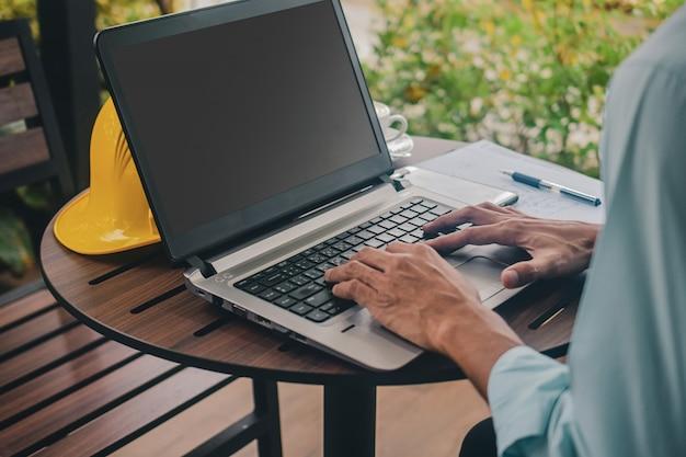 남자는 새로운 정상적인 사회적 거리를 위해 컴퓨터 노트북 작업 양식 집을 사용합니다.