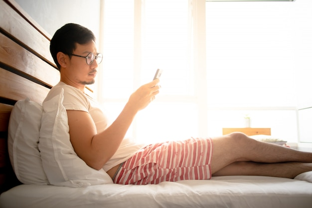 Man use his smartphone and relax on his bed.