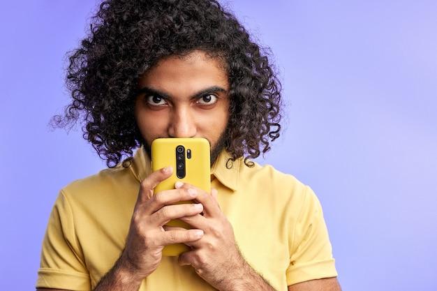 男は携帯電話を使い、顔の近くに持って、何かを隠しているカメラを見て、秘密のメッセージ