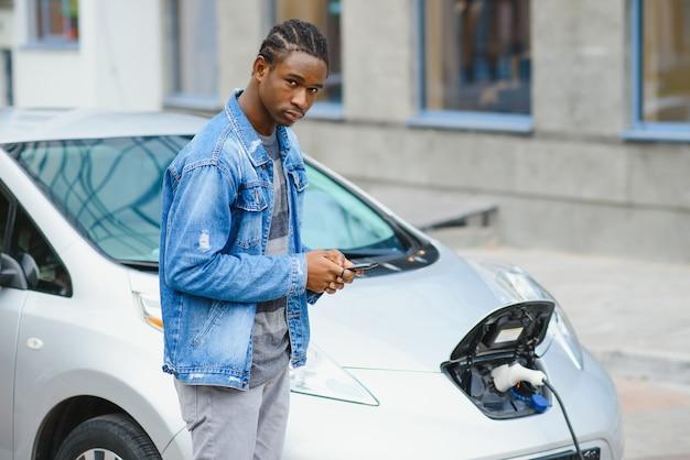 Человек использует смартфон во время ожидания, а источник питания подключается к электромобилям для зарядки аккумулятора в автомобиле