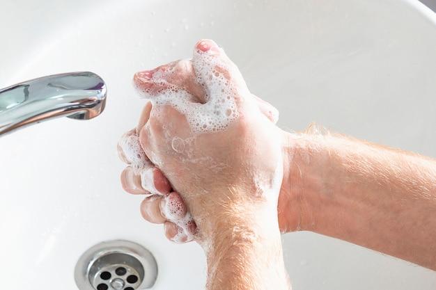 男は石鹸を使用し、水道の蛇口の下で手を洗います。衛生概念の手の詳細。