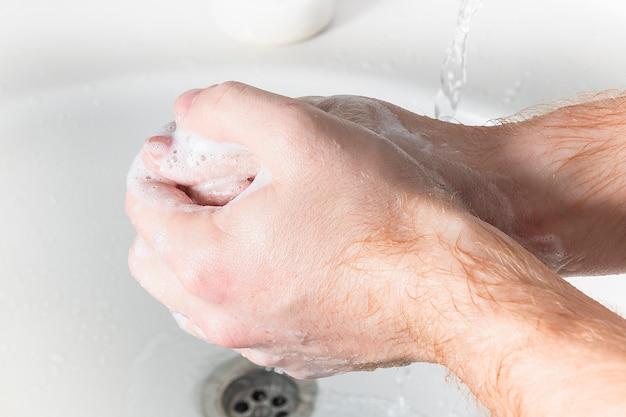 男は石鹸を使い、水道の蛇口の下で手を洗います。衛生コンセプトの手の詳細。