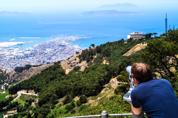 Man use the telescope to see the view of sicily from erice