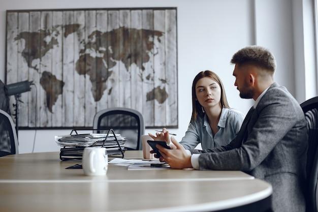 남자는 태블릿을 사용합니다. 비즈니스 회의에서 비즈니스 파트너 사람들이 테이블에 앉아