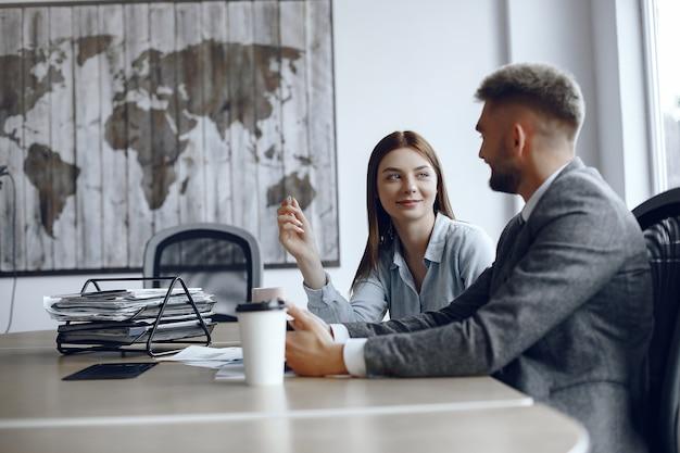 男はタブレットを使用しています。ビジネス会議でのビジネスパートナー。人々はテーブルに座っています。