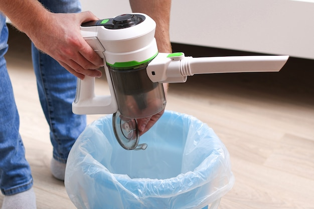 A man uses a bagless vertical cordless vacuum cleaner to clean the floor.