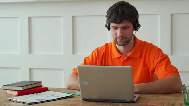 Man uses a headset to talk online at his workplace, confident man sits at the office desk and looks at laptop screen