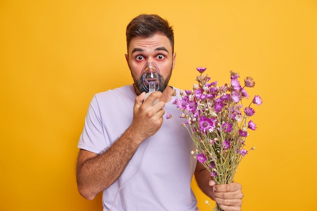 L'uomo usa l'inalatore dai fumi di polline dei fiori farmaci nei polmoni mehas occhi acquosi rossi tiene bouquet di fiori di campo vestiti casualmente isolati su giallo