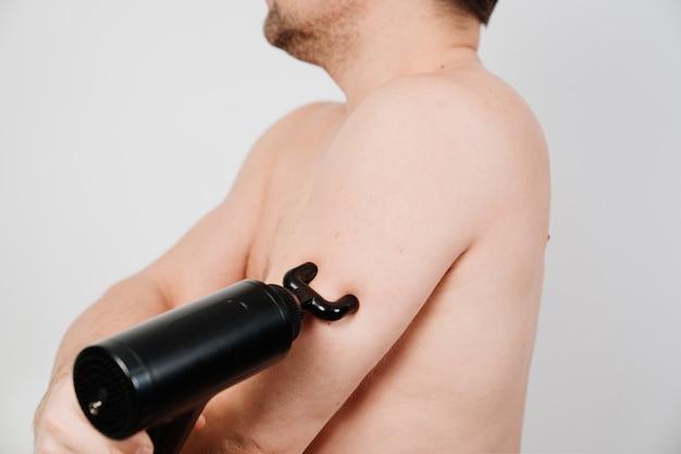 남자는 마사지 총을 사용합니다. 의료 스포츠 장치는 훈련 후 근육통을 줄이고 피로를 완화하며 신체의 문제 부위에 영향을 미치고 피부 상태를 개선하는 데 도움이 됩니다.
