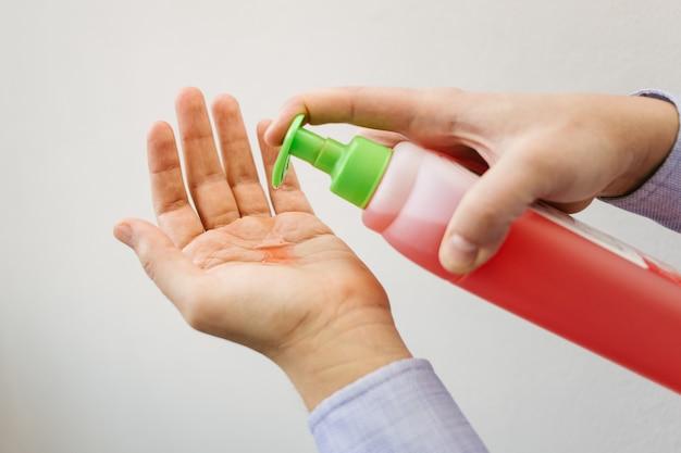 A man uses red antibacterial gel.