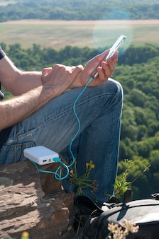 Человек использует смартфон во время зарядки от пауэрбанка
