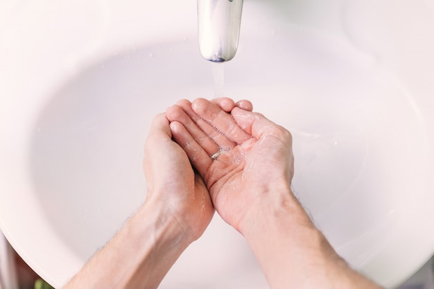 Man uses soap and washing hands under the water tap