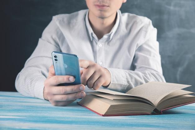 남자는 전화를 사용하고 책을 읽습니다.