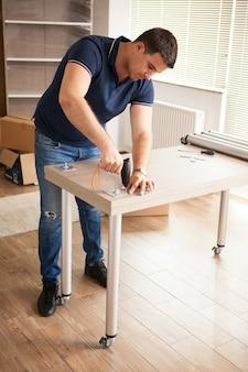 男は道具を使って新しい家の家具を組み立てます。彼はこの家具を新しいアパートのインテリアに使用します。