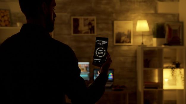 男はスマートフォンの音声起動スマートライトアプリを使用して、家のライトを調整します。将来の技術、音声起動コマンド