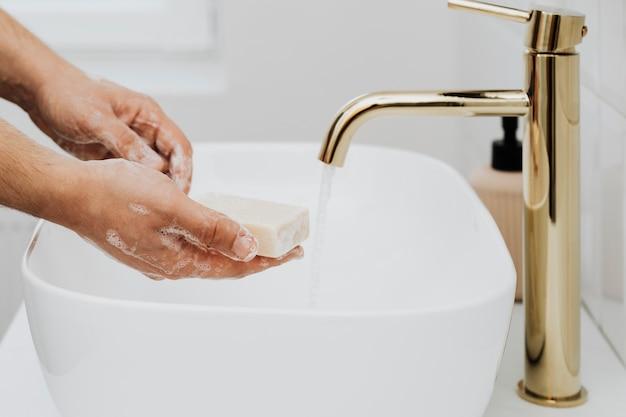 手を洗うために棒石鹸を使用している男