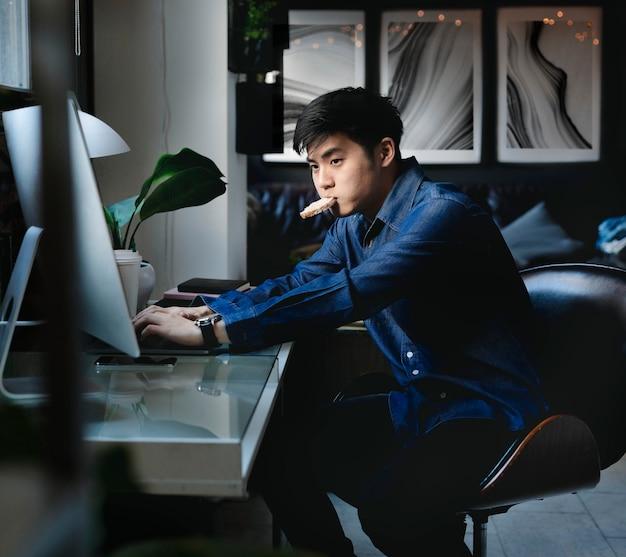 寝室でコンピューターを使用している男性