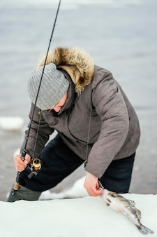 Мужчина ловит рыбу на удочку