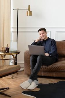 ノートパソコンを使用して自宅で仕事をしている男性