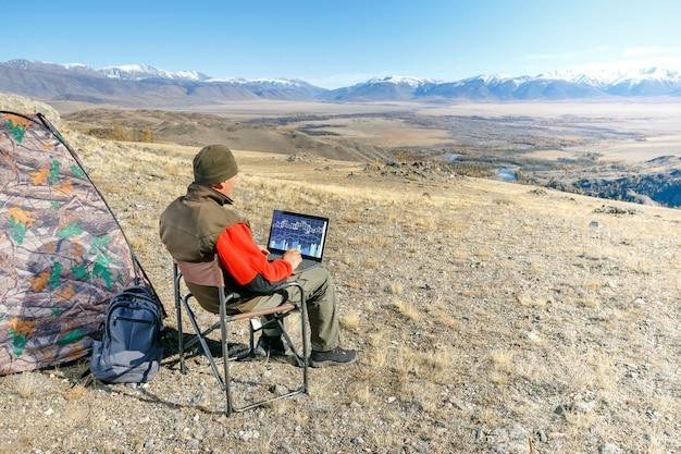 Человек, используя ноутбук в горах