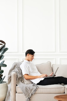 スカンジナビアの装飾のリビングルームのソファでノートパソコンを使用している男性