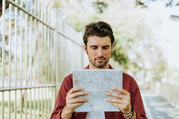 ダウンタウンの公園で地図を使用している男