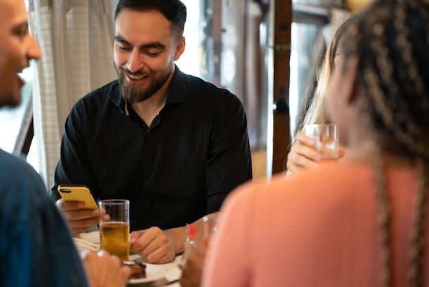 바에서 친구들과 맥주 한 잔을 마시며 휴대폰을 사용하는 남자.