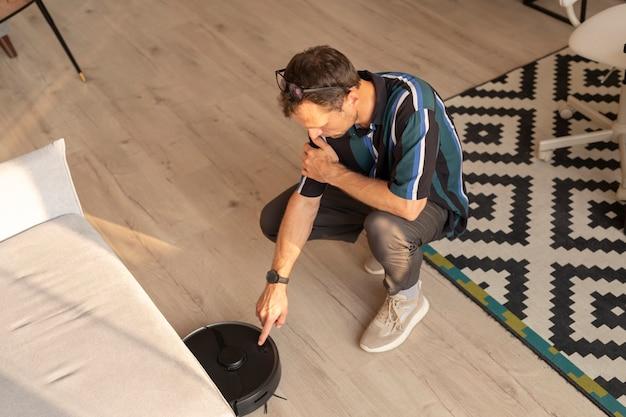 居間でロボット掃除機を使用している男
